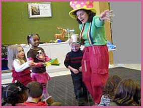 Christmas magician Daisy Doodle throws magic snow on the children at this corporate holiday party