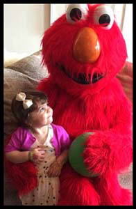 2 year old birthday girl awed by Elmo character entertainment