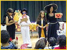 Children dressed up in their Halloween costumes volunteer to participate in a magic trick as part of the kids party entertainment.