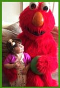 Elmo sits with childrens party birthday girl in nyc