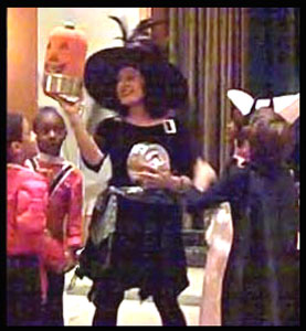 Children awed by pumpkin produced by magician Daisy Doodle at their  Halloween party magic show