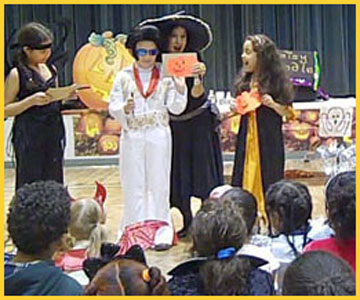 Kids draw and show off their drawings of pumpkin faces at Halloween magic show in Brooklyn NY