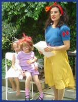 Daisy Doodle, dressed as Snow White princess, leads kids in a playact storytelling kids party game at a childrens birthday party.