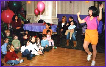 Dora the Explorer character performs for large crowd of children at kids birthday party.