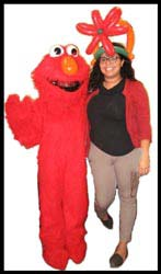 Elmo character went to a big girl's office to wish her a happy birthday.  Don't they make a cute couple?