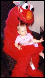 Elmo holds 1 year old child at her birthday party in Westchester NY