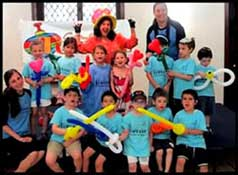 A cheerful group of 3 year and 4 year old kids enjoy Daisy Doodle's toddler party entertainment and balloon twisting at their summer camp in nyc.
