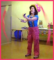 Entertainer Daisy Doodle swings poi balls to upbeat childrens music to begin her toddler show at a party in new york city