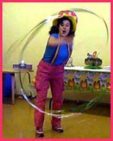 Daisy Doodle waves her big streamer wand to make exciting designs to dramatic kids music to open her toddler party show